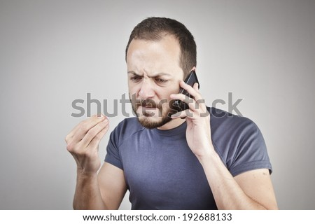 angry young man while answering smart phone not understood - stock photo