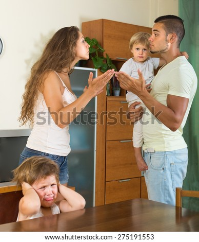 Angry young man with wife and two children having conflict at home - stock photo