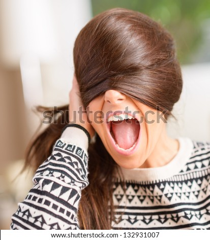 Angry Young Woman Hiding Face With Hair, Indoors - stock photo