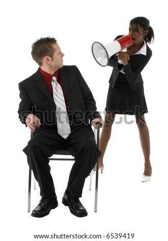 Angry young woman in suit yelling at man through bullhorn or megaphone. - stock photo