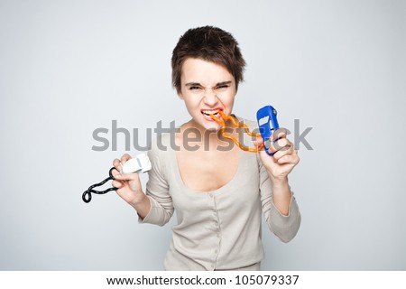Angry young woman squeezing anti-stress toys - stock photo