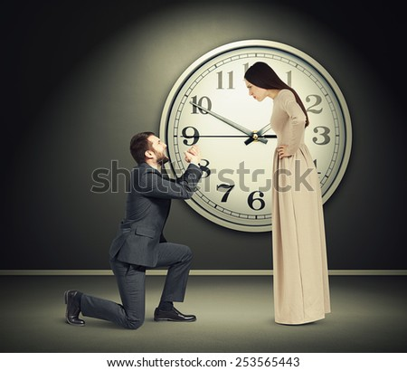 angry young woman staring at latecomer crying man on one knee. concept photo in dark empty room with big white clock on the wall - stock photo