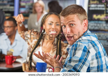 Angry young woman threatening rude man in cafe - stock photo