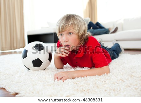 Animated boy watching football match lying on the floor in the living-room - stock photo
