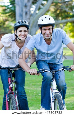 Animated couple riding a bike in a park - stock photo