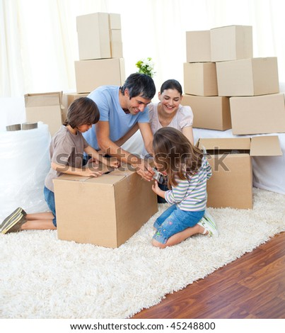 Animated family packing boxes while moving house - stock photo