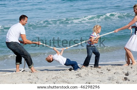 Animated family playing tug of war at the beach - stock photo
