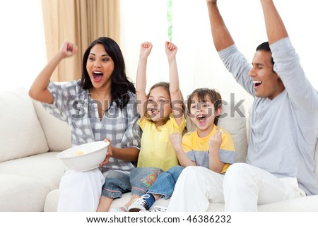 Animated family watching TV on sofa in the living room - stock photo