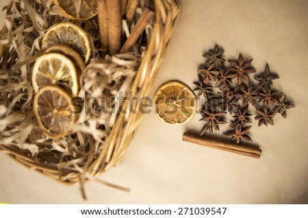 Anise, cinnamon with lemon on kraft paper - stock photo