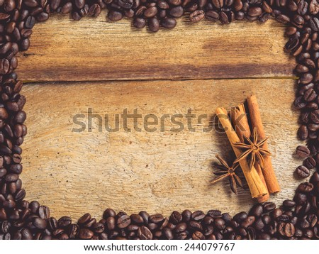 Anise star and cinnamon sticks  in the frame made from roasted coffee beans on wooden background  for text or image : Vintage style and filtered process - stock photo