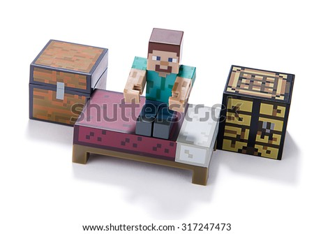 Ankara, Turkey  July 01, 2015: Minecraft figure Herobrine stands on bed isolated on white background.  Minecraft is a game about breaking and placing blocks.   - stock photo