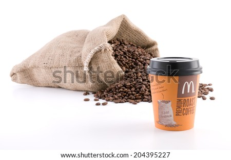 Ankara, Turkey - June 07, 2012: McDonalds coffee cup McCafe in front of sack of coffee beans isolated on white background  - stock photo