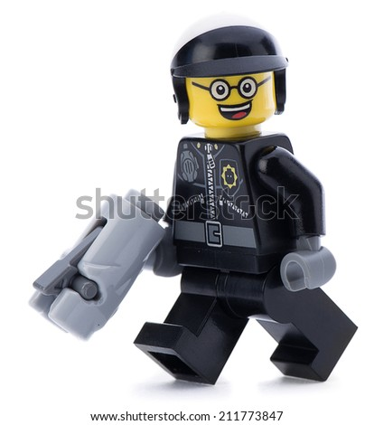 Ankara, Turkey - March 15, 2014 : Lego movie minifigure character good cop with gun walking isolated on white background.  - stock photo