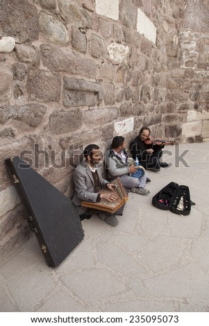 ANKARA, TURKEY - MARCH 30, 2013: Street musicians.Three gypsy musicians playing famous Turkish songs while the visitors enjoying the view and music inside Ankara Castle in Ulus, Ankara. - stock photo