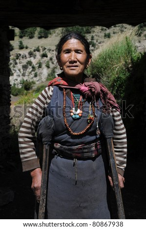ANNAPURNA AREA, NEPAL - OCTOBER 5: Old Nepalese woman smiles to tourist during the main season on the Annapurna trail on October 5, 2010. Majority of the local population are descendants of Tibetan. - stock photo