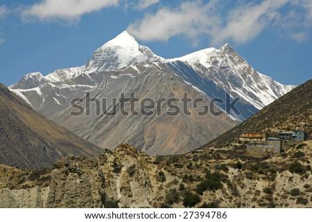 Annapurna mountain range and village on hill - stock photo