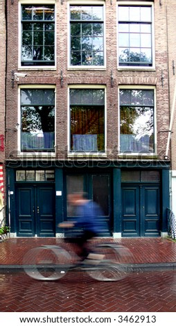anne franks house in amsterdam while a cyclist is going by in front of it - stock photo