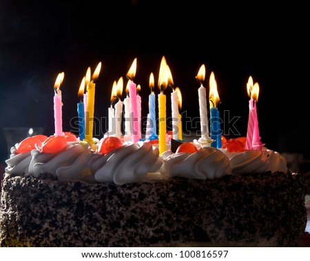 anniversary cake with colorful burning candles in dark - stock photo