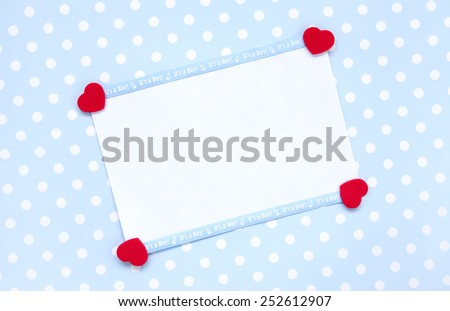 Announcement or invitation. Blank note paper with Its a boy baby blue ribbon, and four red heart shapes on a blue polka dot background.  - stock photo