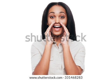 Announcing good news. Cheerful young African woman holding hands around mouth and shouting while standing against white background - stock photo
