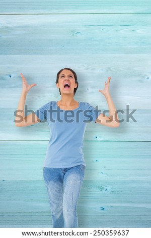 Annoyed brunette gesturing against faded blue wooden planks - stock photo