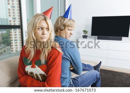 Annoyed couple in Christmas sweaters and party hats sitting back to back at home - stock photo