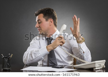 Annoyed indifferent businessman having an uninteresting phone conversation while holding receiver facing the other hand palm in a talk-to-the-hand gesture. - stock photo