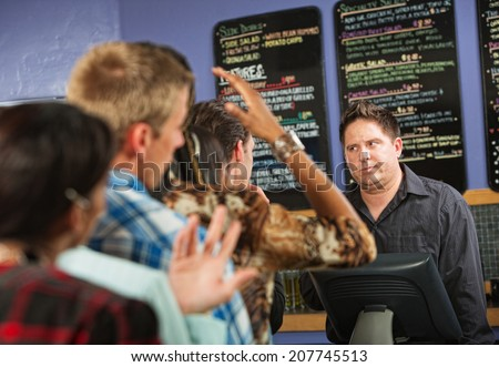 Annoyed male cafe worker with long line - stock photo
