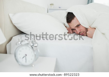 Annoyed man being awakened by an alarm clock in his bedroom - stock photo