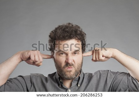 Annoyed mature man plugging ears with fingers - stock photo