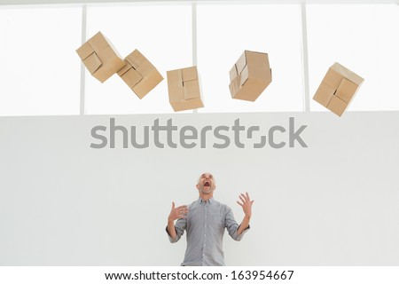 Annoyed mature man with falling boxes standing against white background - stock photo