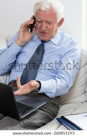 Annoyed senior businessman using laptop and talking on the phone - stock photo