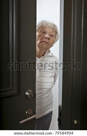 Annoyed senior woman opening front door - stock photo