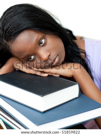Annoyed student leaning on a stack of books against a white background - stock photo