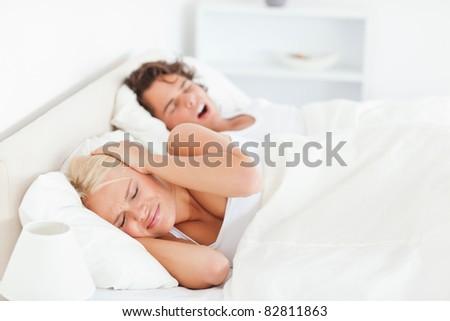 Annoyed woman awaken by her boyfriend's snoring in their bedroom - stock photo
