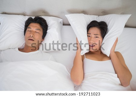 Annoyed woman covering her ears with pillows to block out snoring at home in bedroom - stock photo
