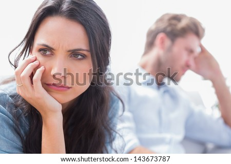 Annoyed woman holding her head next to her husband - stock photo
