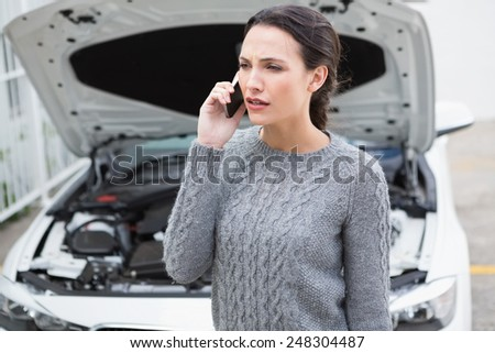 Annoyed woman on the phone beside her broken down car in a car park - stock photo