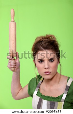 Annoyed woman with a rolling pin - stock photo
