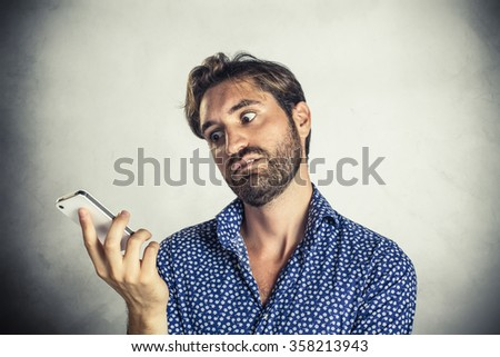 Annoyed young man at mobile phone - stock photo