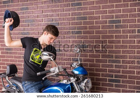 Annoyed Young Man Striking his Sports Motorbike with his Black Helmet Beside a Brick Wall Background. - stock photo