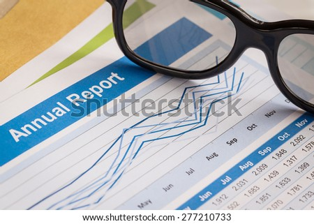 Annual Report letter document and eyeglass - stock photo