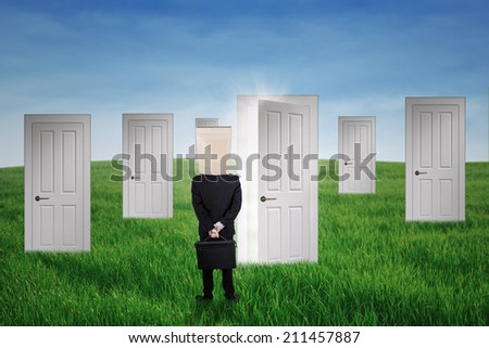 Anonymous businessman standing in front of opportunity doors on the green field - stock photo