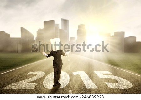 Anonymous businessman with blindfolded walking on the road with numbers 2015 - stock photo