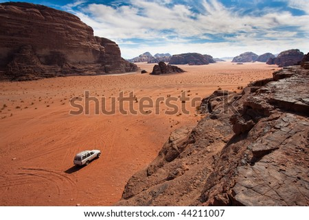 Anonymous car in the sand of Wadi Rum reservation, Jordan. - stock photo
