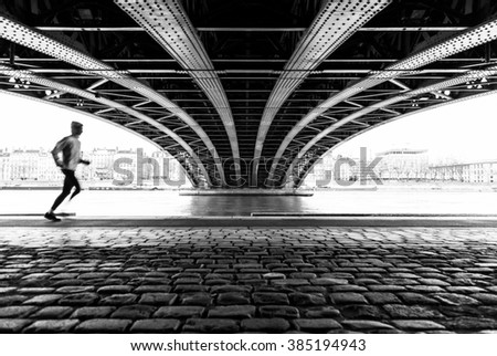 Anonymous male athlete running under a bridge in Lyon on a cold winter day. Sports concept with motion blur and shallow focus. - stock photo