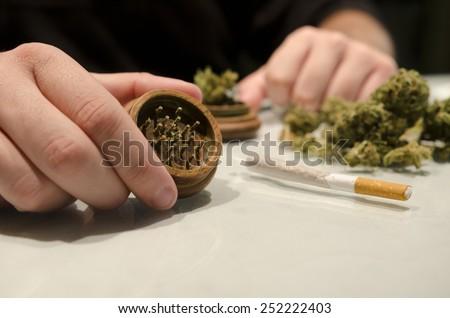 Anonymous man preparing marijuana drug cigar in closeup frame with ambient light - stock photo