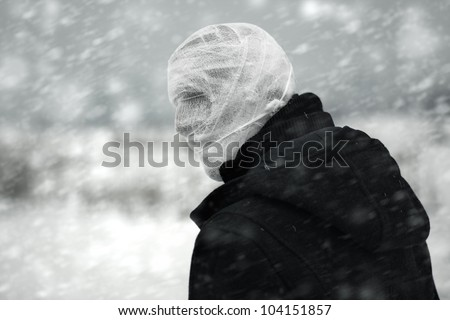 Anonymous person with bandaged head under the nuclear snowstorm - stock photo