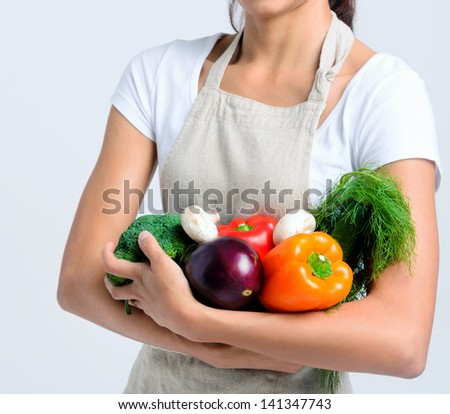 Anonymous woman holding raw vegetables in her arm, peppers, broccoli, dill, mushrooms, aubergine - stock photo