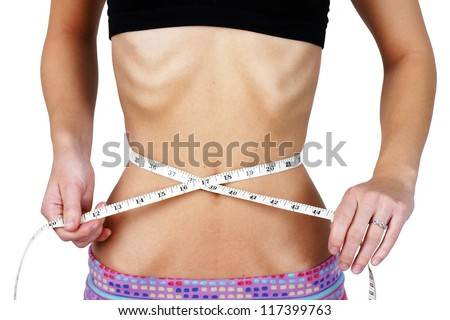 Anorexic and weight obsessed young woman, measuring her very thin and slim waist, torso with ribs and hip bones clearly showing, perfect for mental health and body dismorphia issues. - stock photo